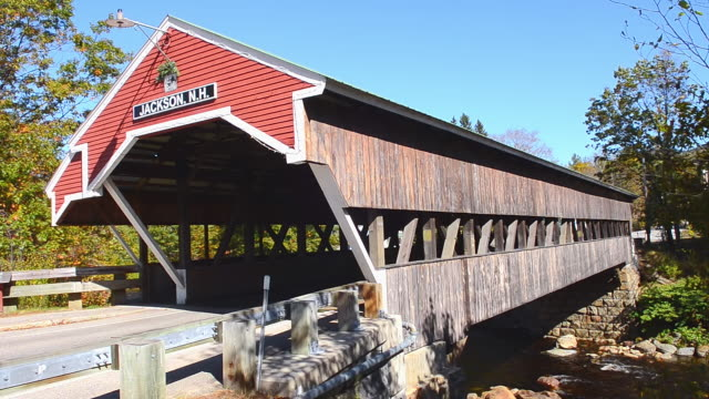 ms shot of bridge 1876 in northern new england in fall foliage in october / jackson, new hampshire, united states - überdachte brücke brücke stock-videos und b-roll-filmmaterial