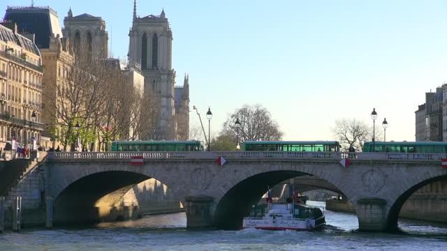 vidéos et rushes de ms shot of bridge and boat on river with cathedral notre dame back side / paris, ile de france, france - bus