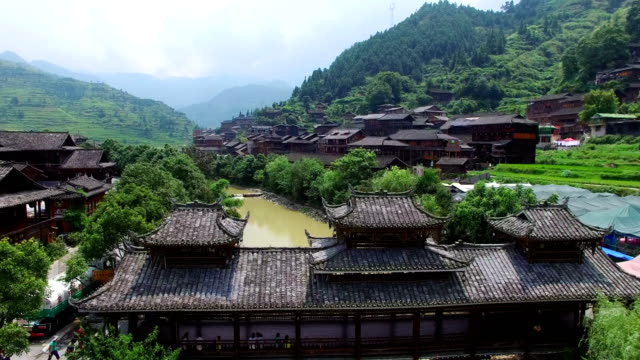ws aerial shot of bridge over a river near xijiang qianhu miao village ,guizhou,china. - wood material stock videos & royalty-free footage