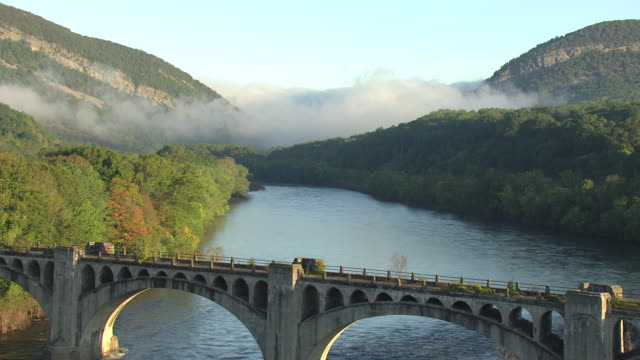 WS AERIAL Shot of bridge with clouds in Delaware Water Gap along Delaware River / Pennsylvania, United States
