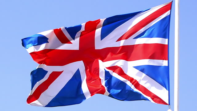 ms slo mo shot of british flag waving in wind / caen, normandy, france - bandiera del regno unito video stock e b–roll