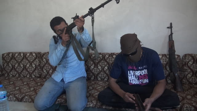 vídeos de stock e filmes b-roll de shot of british jihadists inspecting a gun on a sofa in the city of idblib syria - treino militar