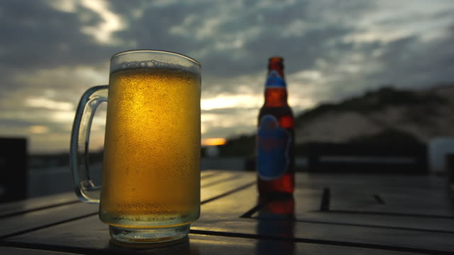 cu shot of bubbles rise in icecold beerglass, sitting on table, with bottle, in front of western pink tinged sky / mui ne, vietnam - beer glass stock videos & royalty-free footage