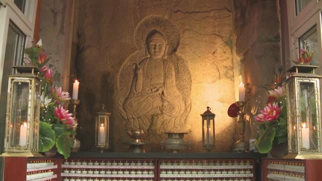 vídeos de stock e filmes b-roll de shot of buddha stone relief in kyubongam temple at mudeungsan mountain - figura masculina