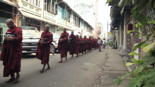 Shot of Buddhist monks walking in single file along a street in Yangon.