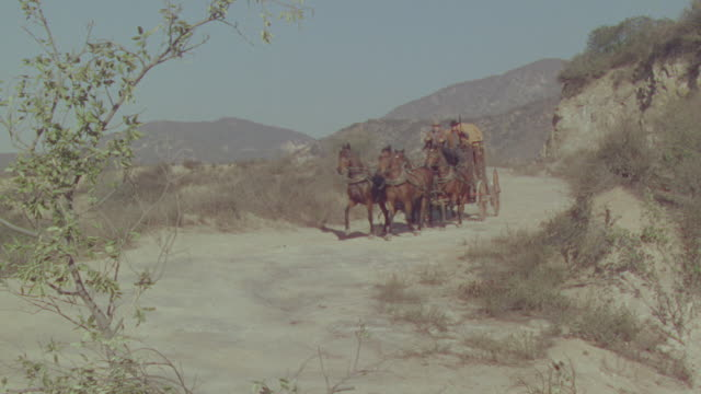 ws ts pan shot of buggy moving through dirt road in desert - vier tiere stock-videos und b-roll-filmmaterial
