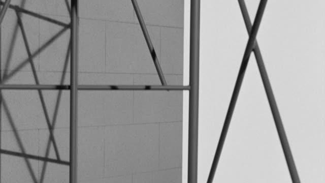 ms pan shot of building under construction along the scaffolding - fahrstuhlperspektive stock-videos und b-roll-filmmaterial