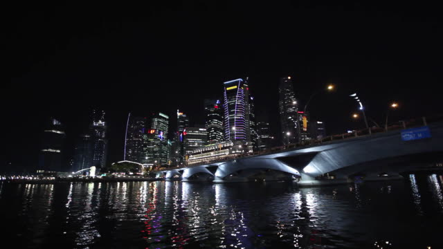 MS POV Shot of buildings and boat passing from under bridge at night / Singapore