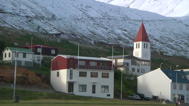 vidéos et rushes de ms shot of buildings at base of snow covered mountain / skagafjorour, nordhurland vestra, iceland  - wiese
