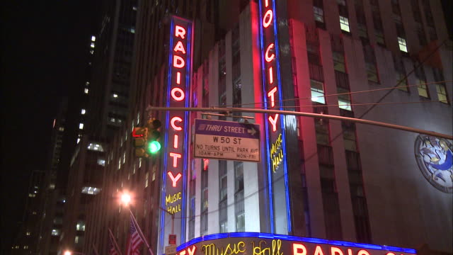 pov shot of buildings at night as seen from a moving vehicle. - radio city music hall stock videos & royalty-free footage