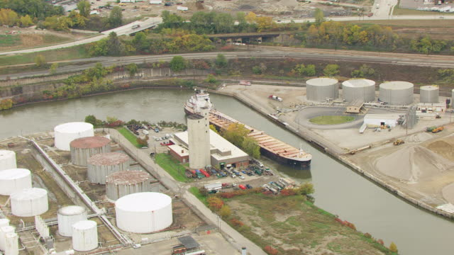 ws aerial shot of bulk carrier calumet in cuyahoga river near oil tank farm / cleveland, ohio, united states - fiume cuyahoga video stock e b–roll
