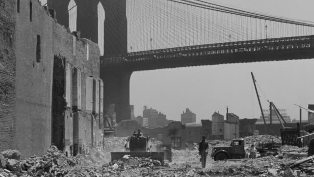 MS Shot of bulldozer working on ground near Manhattan Bridge