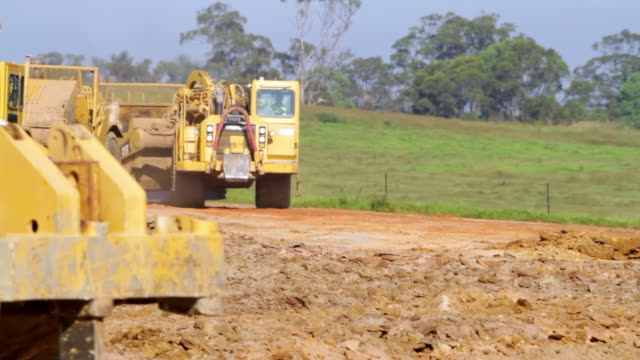 ms pan shot of bulldozer working on site / oran park, new south wales, australia - bulldozer stock videos and b-roll footage
