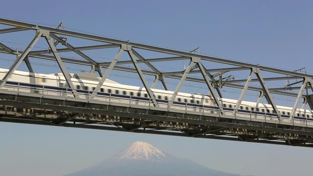 ms shot of bullet train shinkansen passing on bridge in front of snow capped mount fuji / fujigawa, shizuoka prefecture, japan  - mt fuji stock videos & royalty-free footage