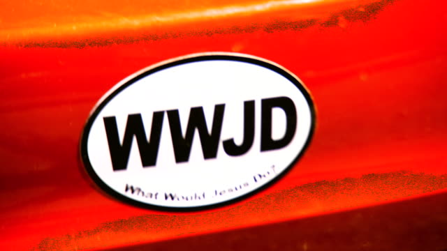 ecu shot of bumper sticker saying wwjd what would jesus do car moves away and sticker goes out of focus / falls church, virginia, united states   - falls church stock videos & royalty-free footage