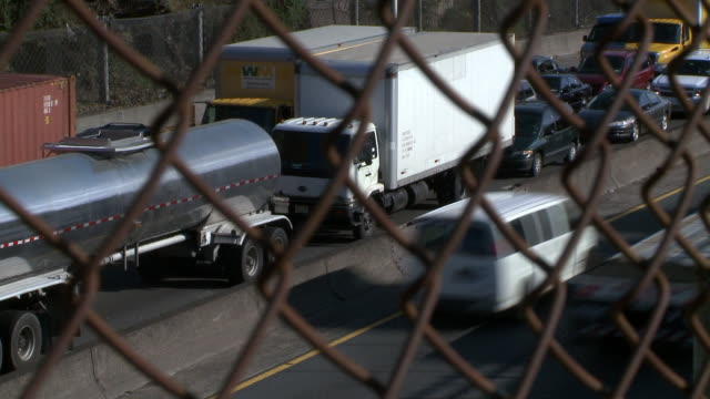 shot of bumper to bumper traffic on the cross bronx expressway through a rusty chain link fence in the bronx during the day - bumper stock videos & royalty-free footage