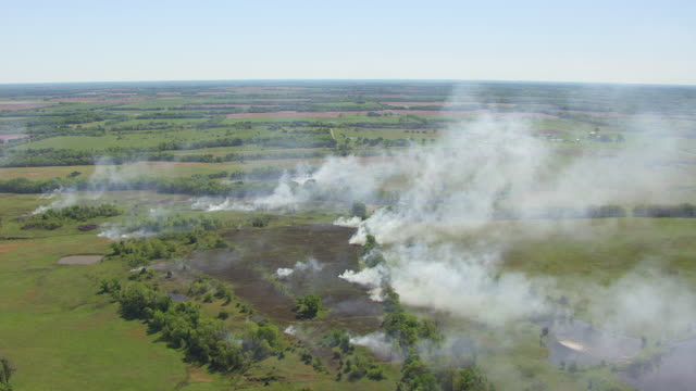 vídeos de stock e filmes b-roll de ws aerial shot of burning fire and smoke on prairie in montgomery county / kansas, united states - kansas