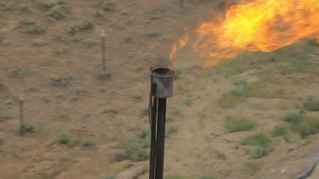 cu aerial ts zo shot of burning flame at fracking site in campbell county / wyoming, united states - fracking stock videos and b-roll footage