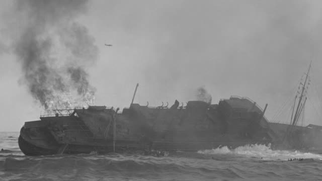 MS Shot of burning ship sinking in water