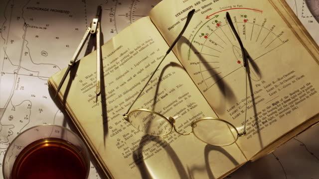 MS ZI ZO Shot of Burning the midnight oil, Seamanship book open on marine chart with glasses & deviders, Navigation / Estepona,Espana, Malaga, Spain