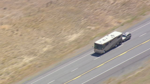 ws aerial ts zo shot of bus running on road in desert / wyoming, united states - wyoming stock videos & royalty-free footage