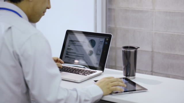 ms tu shot of business man is working in casual office with beside digital tablet and laptop / kyoto, japan - ホワイトカラー点の映像素材/bロール