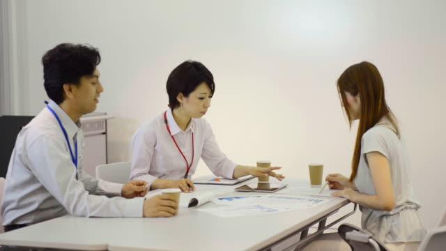ms pan shot of business person of three people have meeting in meeting room with digital tablet / kyoto, japan - engångsmugg bildbanksvideor och videomaterial från bakom kulisserna