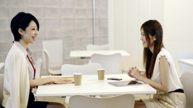 ms shot of business woman of two people are relaxing in break room / kyoto, japan - fare una pausa video stock e b–roll