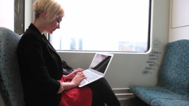 MS Shot of Business woman working on laptop on train / Berlin, Germany