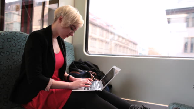 ms shot of business woman working on laptop on train / berlin, germany  - transportation building type of building stock videos & royalty-free footage