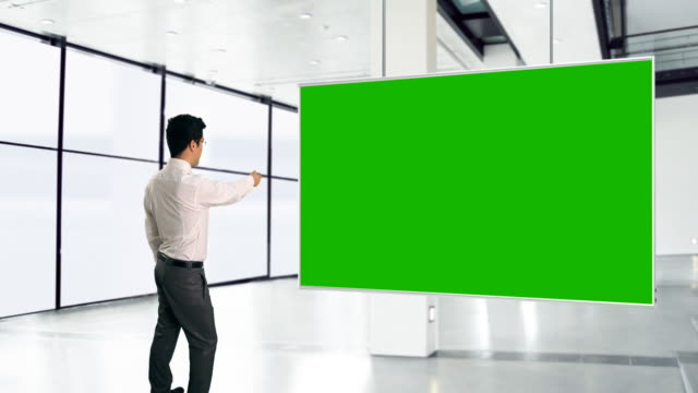 stockvideo's en b-roll-footage met ms shot of businessman with green screen and remote control / bergen, hordaland, norway - digitaal samengesteld beeld