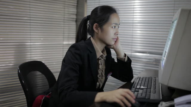 ms pan shot of businesswoman using computer in office / xi'an, shaanxi, china - hand am kinn stock-videos und b-roll-filmmaterial