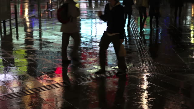 MS Shot of Busy pedestrian street reflections on rainy night in Akihabara / Tokyo, Japan