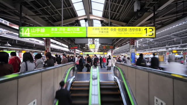 ms t/l shot of busy platform with crowds of people boarding trains and using escalators at shinjuku station / tokyo, japan - railway station platform stock videos & royalty-free footage