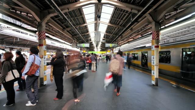 ms t/l shot of busy platform with trains pulling in and out at shinjuku station / tokyo, japan - 鉄道のプラットホーム点の映像素材/bロール