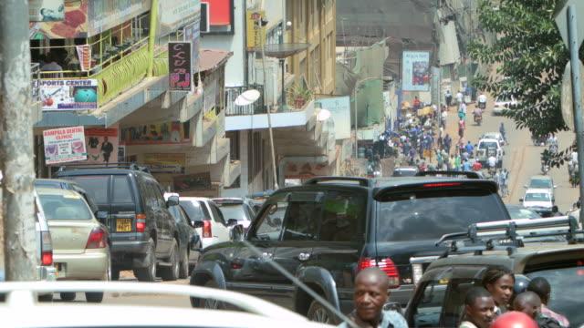 ms shot of busy street with cars, motorbikes and people / kampala, uganda - kampala stock videos & royalty-free footage