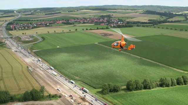 ws aerial shot of calidus auto gyro car flying over highway and farm land / hildesheim, lower saxony (niedersachsen), germany - flugzeug in der luft stock-videos und b-roll-filmmaterial