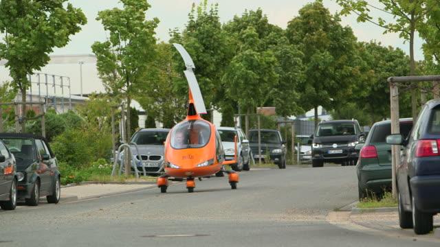 vídeos y material grabado en eventos de stock de ms pan shot of calidus auto gyro flying car driving on road following car / hildesheim, lower saxony (niedersachsen), germany - invento