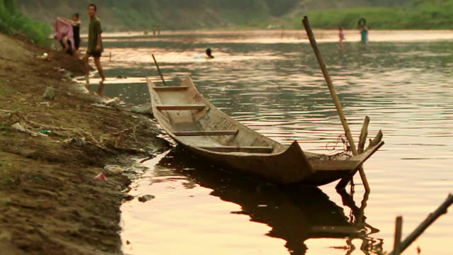 ms slo mo shot of canoe moored on river bank in sunset light / luang prabang, laos - travelling light stock videos & royalty-free footage