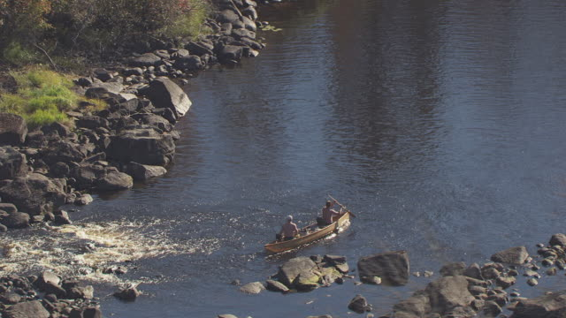 ms aerial zo shot of canoers going through rocky rapids and pull out to reveal forest / minnesota, united states - 樹林点の映像素材/bロール