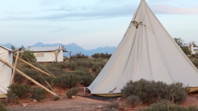 ms pan shot of canvas tents at bottom of the mountains / monument valley, utah, united states  - native american reservation stock videos & royalty-free footage