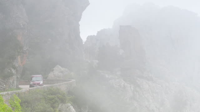 ms shot of car drives on road through mountains of calanche of piana in fog, unesco world heritage site / porto, corsica, france - カランシェ点の映像素材/bロール