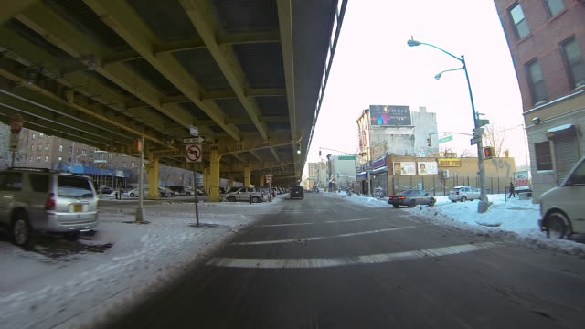 ms pov shot of car mountdriving on snow covering street past parking lot under bridge / brooklyn, new york, united states - incidental people stock videos & royalty-free footage