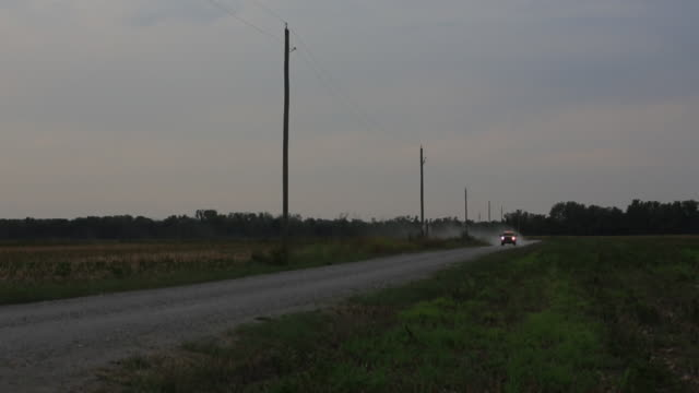WS Shot of car moving on Country dirt road through farm land / New York, Kansas, United States