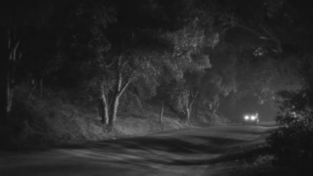 MS PAN Shot of car moving on road through rural area and stop with flat tire at night