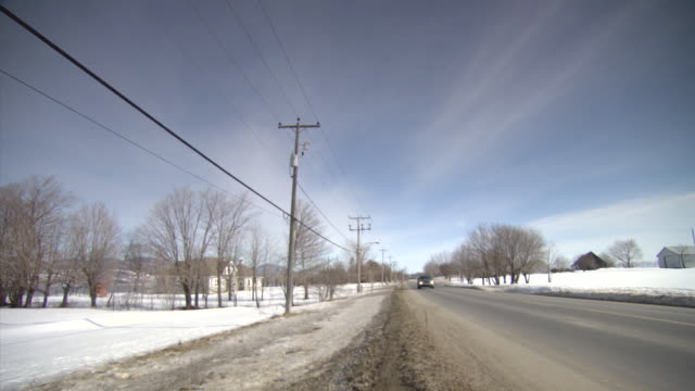 ws shot of car moving on road through snow covered road side / quebec, canada - straßenrand stock-videos und b-roll-filmmaterial