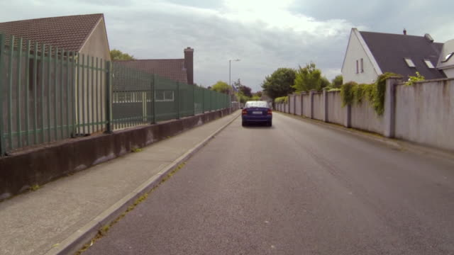 pov shot of car on street amidst fence and surrounding wall in town against sky - galway, ireland - surrounding wall stock-videos und b-roll-filmmaterial