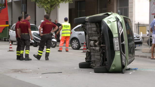 ws shot of car overturned in middle of road with rescue of firefighters / isernia, molise, italy - verkehrsunfall stock-videos und b-roll-filmmaterial
