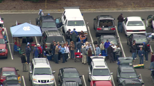 ms aerial shot of car parking area with people on wallace wade stadium / north carolina, united states - gemeinsam gehen stock-videos und b-roll-filmmaterial