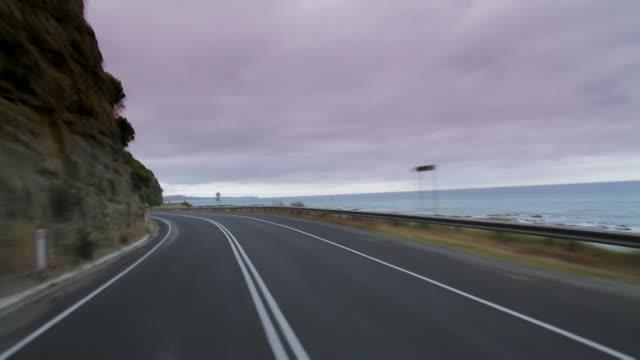 ms pov t/l shot of car speeding along great ocean road for classic coastal drive / melbourne, victoria, australia - coastal road stock videos & royalty-free footage